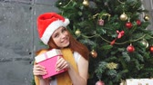 bolsa de compras : Young woman with santa hat holding a shopping bag. Stock Footage