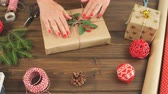 шпагат : High angle view of Christmas gift box wrapped in craft paper and tied with plain bakers twine on the dark wooden planks with decorating elements Holidays and Gifts concept. Стоковые видеозаписи