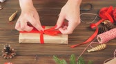paketlenmiş : Female hands tying knot on giftbox and different Christmas symbols Stok Video