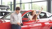 таверна : Happy caucasian couple chooses their first family car to buy in a showroom. Successful businessman asking his beautiful red-haired wife whether she likes it or not.