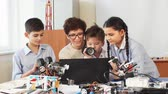 integrace : Curious clever pupils with the help of their female teacher doing a group project programming homemade robot using laptops on extracurricular classes Dostupné videozáznamy