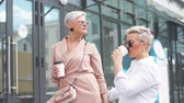 realtor : Happy businesswomen with coffee cup conversing outside office building