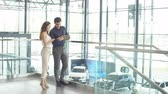 kitapçık : Attractive young couple of european appearance reading a booklet at the dealership showroom choosing a car.