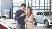 közlekedési mód : Buying their first car together. Young caucasian positive couple of successful businessman and his wife hugging near red glistering car in car dealership, man holds the key from their new car