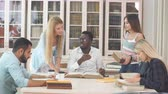 referência : Pensive african american young man in stylish eyeglasses for vision correction, Arab man and three euopean young female students reading big old textbook sitting at the table against window .
