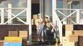 remoção : Young couple with book sitting on steps while moving in new home