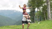 разработка : Athletic woman doing exercise with her male partner outdoors over high mountains in background