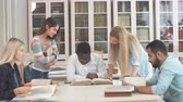 dayanışma : Mixed-race group of university students with a focus on blonde caucasian woman doing linguistic researches, turning over the pages of big old reference textbook at library.