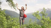 sobrevivência : Traveler Man with backpack raised hands. mountains landscape on background Lifestyle Travel, happy, emotions, success concept. Slow motion