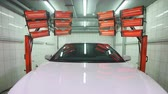 myjnia samochodowa : Red lamps for drying the ceramic coating are behind car