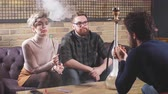 табак : Attractive young men and woman are talking while smoking the hookah. Entertainment and conversation concept Стоковые видеозаписи