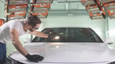 buffing : Man checks result of polishing of car with a flashlight