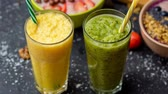 druif : Vers gemengd fruit smoothies in glazen. Gele, groene drankjes. close-up video