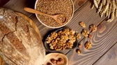 sesame seed : Bakery - gold rustic crusty loaves of bread and buns on wooden cutting board decorated with healthy cooking ingredients, seeds, nuts and raisins and figs