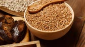 sesame seed : Flat Lay of different kinds of organic bread isolated on wooden table. Fresh sourdough artisan bread, loaf of rye bread with linseed and chopped pieces of buckwheat bread with nuts on chopping board. Stock Footage