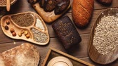 sesame seed : Whole grain, whole loaf and sliced pieces of multigrain bread contains whole grains poppy, millet, flaxseed, pumpkin seeds, and sunflower seeds isolated on dark wooden table . Stock Footage