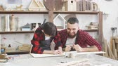 teach : Young father is keen on making DIY wooden toy together with his son on carpentary masterclass in woodworking studio. Dad is helping his son to mark up lines on wooden plank with ruler