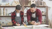 barbear : Dad and son looking at smart phone together while choosing a model for creating a family masterpiece standing in the carpenter s workshop surrounded with tools ans wooden figures.