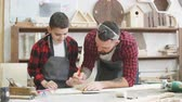 crafting : Young father is keen on making DIY wooden toy together with his son on carpentary masterclass in woodworking studio. Dad is helping his son to mark up lines on wooden plank with ruler