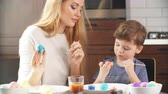 Woman Decorating Easter Eggs with Little Son. Easter celebration concept.