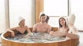 Group of male and female friends visiting bathhouse in holidays, being overjoyed and happy, enjoying jacuzzi in hot wooden round barrel Stock Footage
