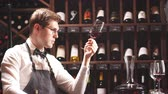 bağcılık : Handsome and young smiling brown haired sommelier with a bottle of wine on the background of dark wine house with shelves of bottles with alcohol Stok Video