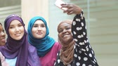 hijab : Group of four Asian and African Muslim women in fashionable traditional clothes taking selfie in shopping mall.