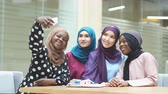scarf : Group of four Asian and African Muslim women in fashionable traditional clothes taking selfie in shopping mall.