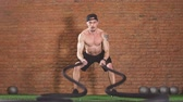 squatting : Shirtless strong athlete being concentrated on the exercise with battle rope requiring increased effort and strength. Cross Fit concept, Slow motion Stock Footage