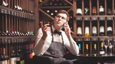 appreciation : Elegant young sommelier talking on the phone with the buyer in a wine boutique