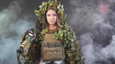 bojiště : Heavily armed female soldier in battle helmet and ghillie suit holding assault rifle isolated on dark smoky battlefield. Paint ball and laser tag sport games