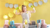 anonym : Cheerful blonde housewife in gray apron in green gloves showing biceps isolated on yellow background. Happiness, Winner of contest.