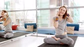 pose : Happy young woman talking on smartphone in yoga room. Filmati Stock