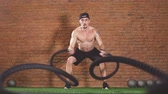 funzionale : Determined shirtless male athlete performing waves by battle rope, keeping fit in crossfit club, slow motion Filmati Stock