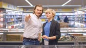go cart : Young happy couple in the supermarket choosing products for a family celebration.