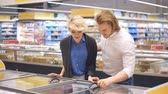 refrigerador : Happy caucasian couple choose frozen foods from the supermarket refrigerator. Family shopping at trading centre in a grocery department. Stock Footage
