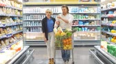 érv : Couple in a supermarket shopping equipped with a shopping cart buying groceries and other stuff, they are looking for what they need Stock mozgókép