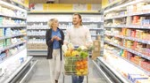go cart : Positive family customers with full trolley of healthy organic vegetables and fruits in grocery store during weekly food shopping