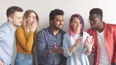 divers : Group of Multicoloured joyful people standing against white wall. Caucasian woman with violet hair showing photos on smartphone to her diverse friends. Stockvideo