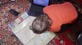 bez domova : A little boy sitting on the floor in the children room at home and trying to do homework with a computer, maps, magnifier and globe. New generation, technology and new school education Dostupné videozáznamy