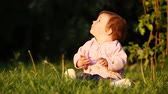 Happy little baby-girl seated on the green grass in the park at sunset. Vídeos