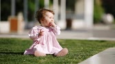 Happy baby-girl seated on the green grass in the park and playing. Vídeos