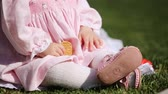 Close-up of the beautiful baby-girl seating on the green grass in the park.