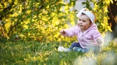 Little pretty baby-girl sitting on green grass in the park at the sunsat. Vídeos