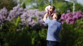 Happy father holding little baby-girl in arms and playing together in the park.