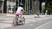 Rear view of the little girl on a bicycle in summer park in the sunshine day. Vídeos