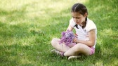 Close-up of happy little girl braiding wreath from flowers on the meadow.