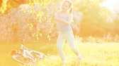 blossom : Happy little girl are dancing on the meadow at bright sunshiny day.