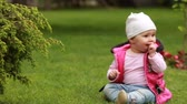 Cute smiling baby-girl crawling on a green grass in the city park. Vídeos