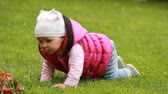 Cute little baby-girl is crawling in the green fall-meadow in the city-park.